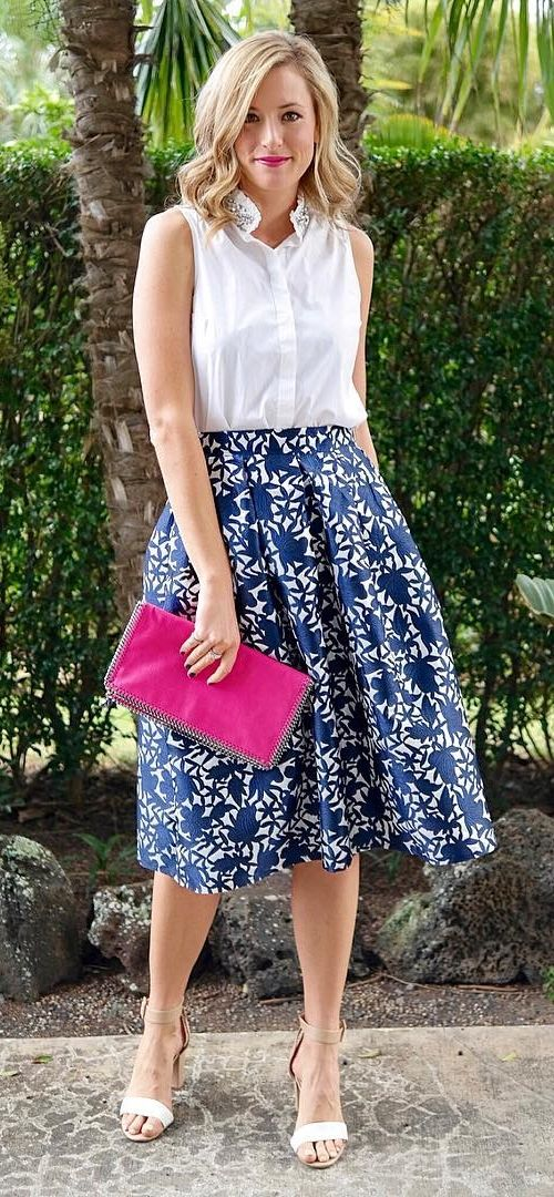 A printed skirt with a white blouse paired with a bold pink clutch.