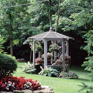Small Gazebo, Big Effect - Even a small gazebo can have a big impact. The 6-1/2-foot-wide structure offers a great getaway at the edge of a wooded area and a view back toward the elaborately landscaped house. Plants fill the gazebo with color and fragrance.  bhg.com