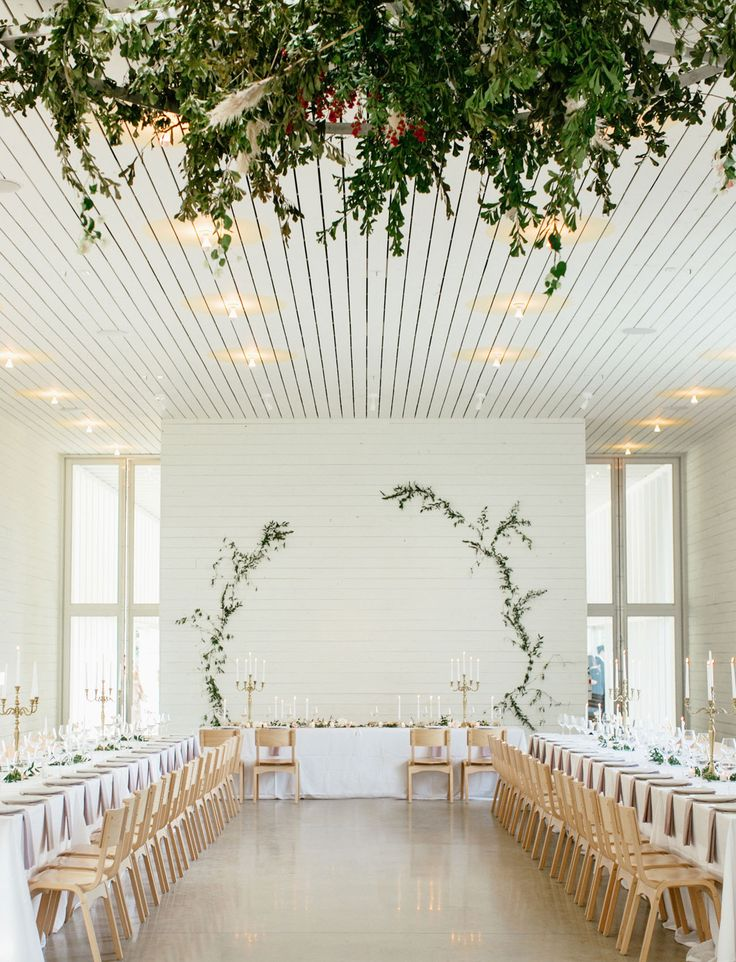 This climbing vine wall frames the simple + white interior perfectly. With clean lines and Scandinavian inspired design elements, this elegant and modern wedding reception is utterly gorgeous.