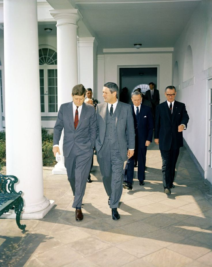 1961. 24 Mars. KN-C17371. President John F. Kennedy Walks with Secretary of the Navy John Connally, Vice President Lyndon B. Johnson, and Others. Photographer: Knudsen, Robert. Photographer, Captain Cecil Stoughton, stands in back, between President Kennedy and John Connally. West Wing Colonnade, White House, Washington, D.C.