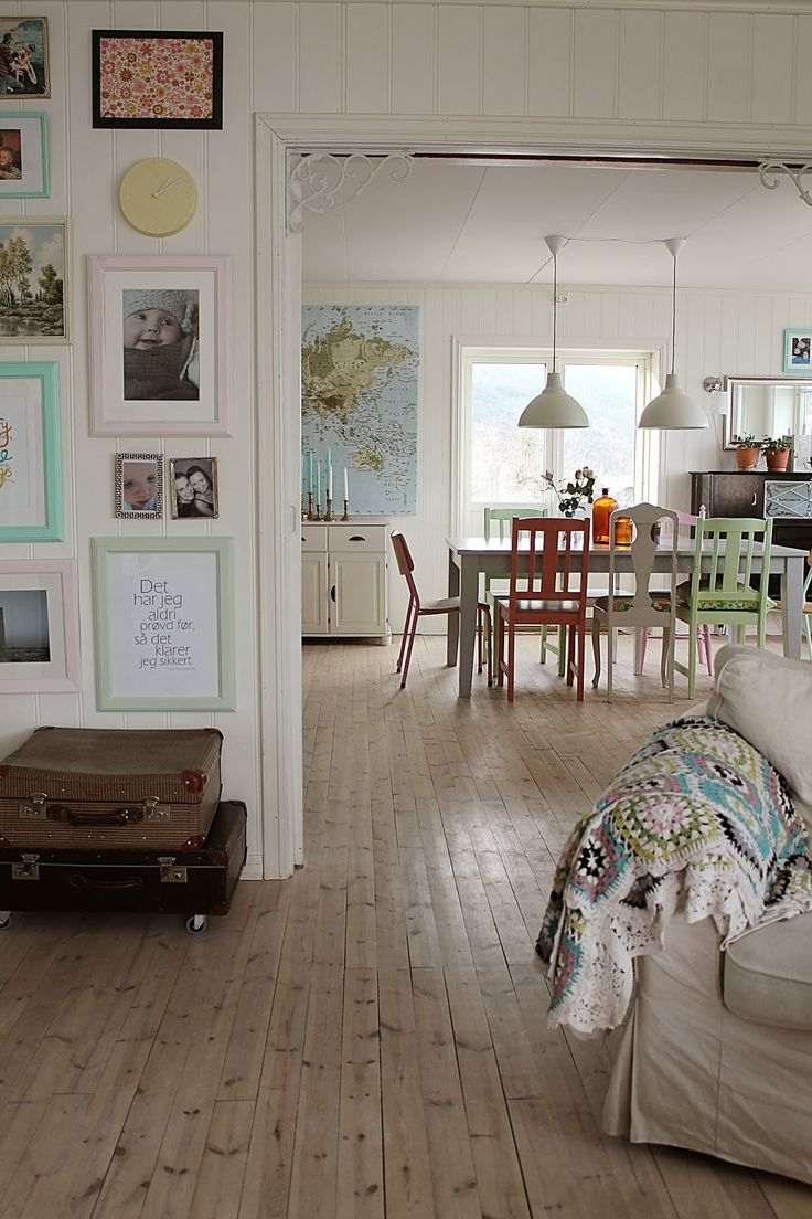 Love the photo gallery wall and mismatched painted chairs