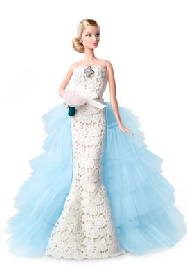 """2016 ~ Oscar de la Renta Barbie. Inspired by the runway """"Something Blue"""" bridal look, Barbie® doll is a take-your-breath-away vision in this ivory, embroidered lace over chiffon trumpet gown. The simplicity of the gown's fluid lines, and tiers of the wispy light blue train flowing behind her, personifies the designer's passion for interpreting romance in a stylish modern way."""