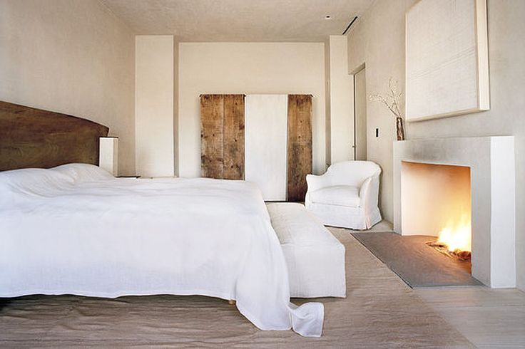 the panel on the back wall is a wardrobe with one panel whitewashed. above fireplace is a framed panel of antique linen that covers a flat screen  TV.  Meh to TV being in a bedroom, but it's a hotel so I guess they get a pass. :-) Axel Vervoodt design - of course.
