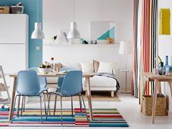 Séjour/salle à manger ouvert et coloré avec une table en bois clair et des chaises bleues.
