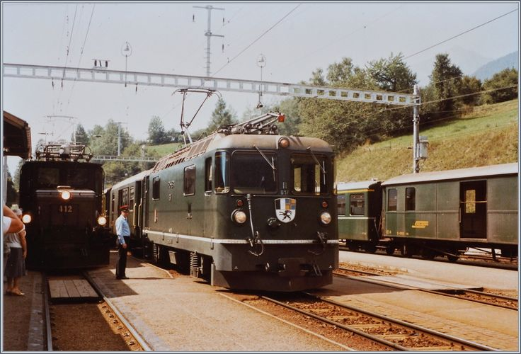 In the summer of 1984, most of the RhB locomotives and cars were still green.  In Filisur the Ge 4/4 II 617 waits with its fast train 557 from Chur to St.Moritz to the journey, on the right in the picture the connection train to Davos is recognizable and on the left in the picture the Ge 6/6 I 412 with a freight train awaits.  20 August 1984