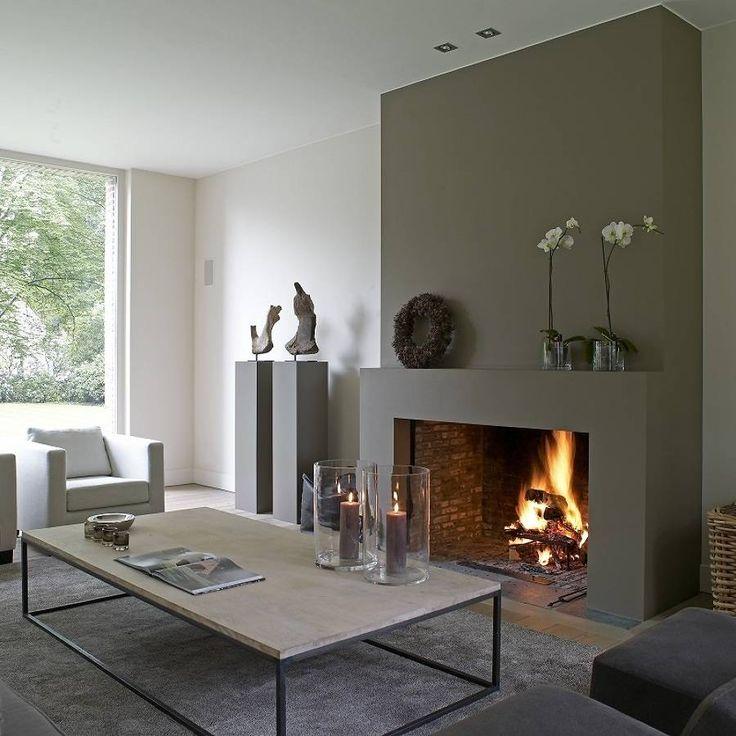 Camino classico a legna per un salotto contemporaneo moderno con le pareti verde scuro - grigio