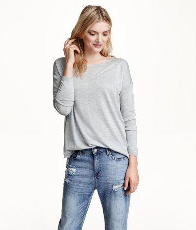 드롭 숄더 스타일의 긴소매 루즈핏 파인니트 스웨터. 와이드 네크라인, 뒷면이 좀 더 긴 라운드 아랫단.