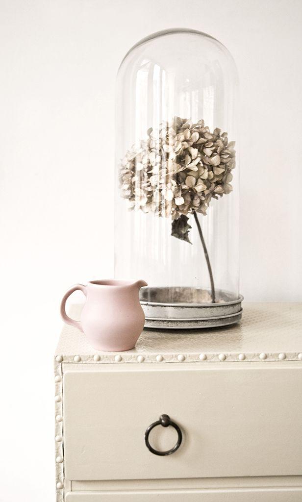 Romantische styling met gedroogde bloemen onder een stolp en een aardewerk melkkannetje.