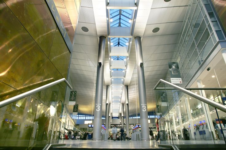 Insinde Terminal 3 at Copenhagen Airport. The significant number of 22 meter high pairs of columns that run through the building provides space for the light, creating a feeling that is almost monumental. The design also makes the great space uncluttered and easy to navigate in.