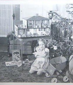 A Christmas Dollhouse, baby doll, buggy... Such a happy little girl! And she must have been a very good little girl for Santa to be so generous. A sweet moment to remember always.