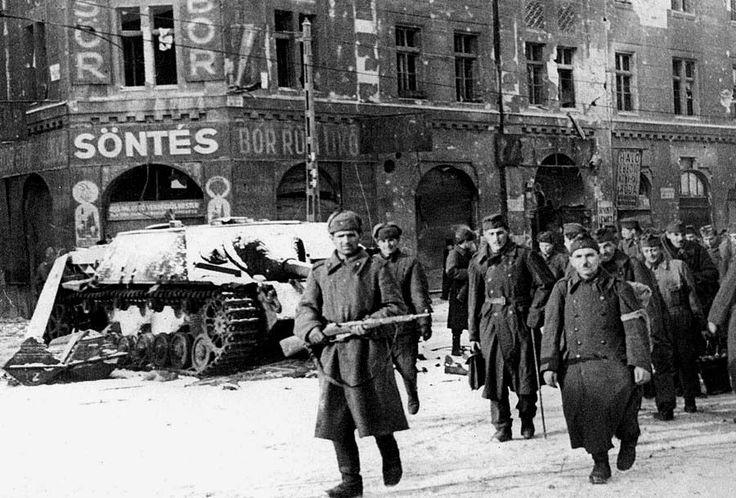 Budapest, février 1945 : des prisonniers Bulgares escortés par des soldats Russes passent devant la carcasse d'un Panzer IV/70 appartenant à la Panzer-Division Feldherrnhalle.