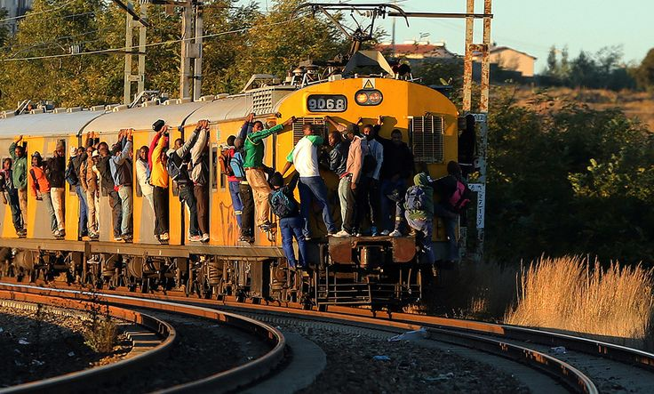 "Commuters hang onto a moving passenger train in Soweto, South Africa. As South Africa marks the 20th anniversary of multiracial democracy on Sunday, the achievements and soaring expectations of what was dubbed a ""rainbow nation"" have been tempered by a different inequality - the yawning gulf between rich and poor."