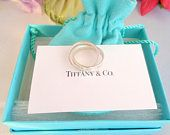 Reduced Authentic Sterling 925 Tiffany & Co 1837  Interlocking Rings.The Ring is a Size 5 One of the Rolling  Rings says Tiffany & Co 1837 Perfect to wear with on your Pinkie. Comes in Blue Tiffany Pouch, a Hard Blue Tiffany Box and a Bag from Tiffany with the White Handles. Perfect for a Gift. The white card is for display only. It has the Care Instructions for Sterling Silver. It is written out in the listing.  CCCsVintageJewelry.com Price $99.99