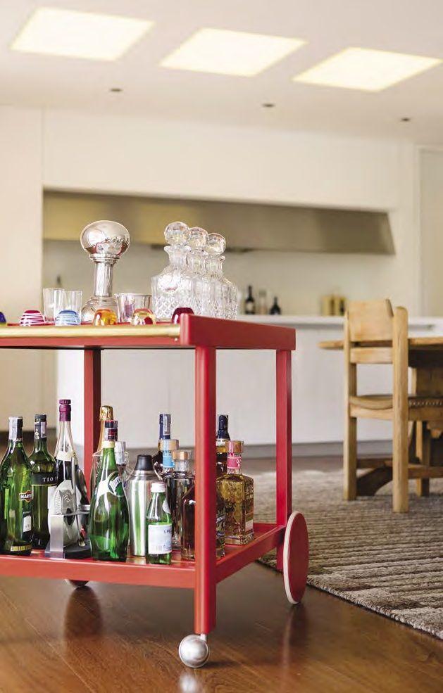 El mueble bar con ruedas es un complemento imprescindible; el color rojo es muy acertado para contrastar con el blanco y la madera