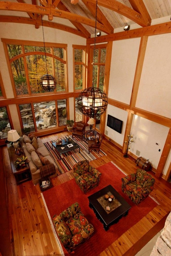 A High Wooden Ceiling Design With Wide Glass Windows And Beautiful Hanging  Lamps Above The Living