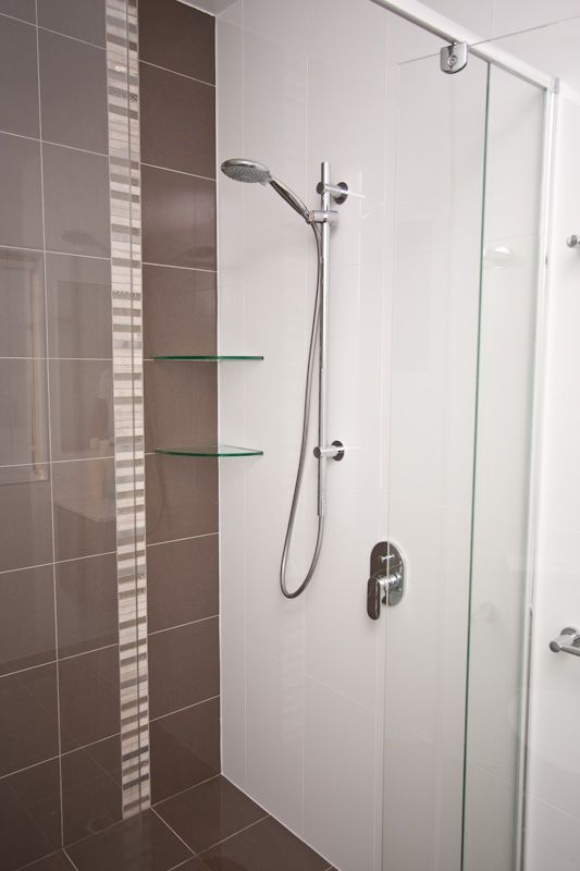 Feature tiles and glass shelving turn a shower into a functional and stylish statement. wwww.onecallkitchens.com.au