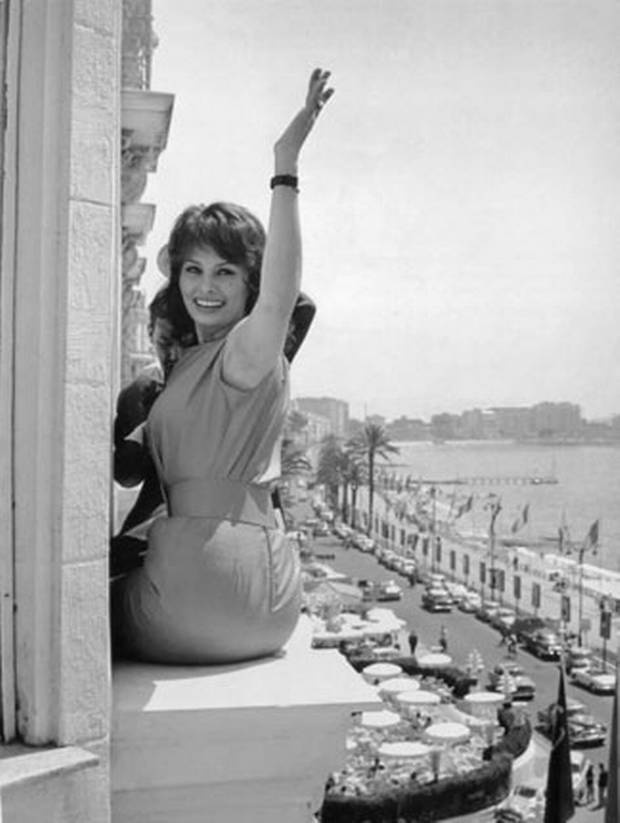 Film star Sophia Loren poses on the window ledge of her hotel whilst she pr - The Independent