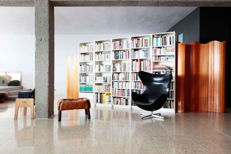 Loft: Spacious Pallars Loft Interior with Minimalist Style in Barcelona, Spain by KAYSERSTUDIO, Adorable Reading Room Area in Pallars Loft by KAYSERSTUDIO showing Black Lounge Chair and Tufted Leather Ottoman and White Bookshelf Unit also Brown Room Dividers