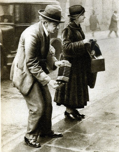 A London street entertainer plays his concertina, in the 1920s.