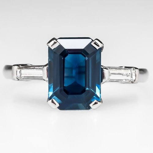 Emerald Cut Blue Sapphire Engagement Ring This lovely blue sapphire engagement ring is centered with a 1.70 carat emerald cut center stone. The sapphire is a true blue color and is lovely. Channel set into each shoulder is a high quality baguette cut diamond accent. The ring is crafted of solid platinum and is in very good condition.
