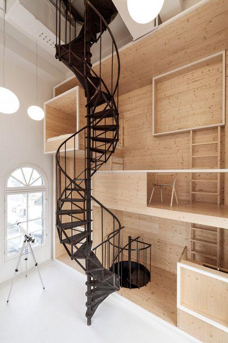 """Dutch artist Maarten Baas will be the first resident of this studio with a spiral staircase, created by interior architects i29   """"Room On The Roof wil de kunstenaar een unieke ervaring bieden"""", zei Maarten Baas in een verklaring. De ruimte brengt twee werelden bij elkaar. Er wordt hier gespeeld met schaal en beweging, geïnspireerd op het sprookje Alice in Wonderland.https://www.dezeen.com/2015/01/26/i29-room-on-the-roof-artists-residence-studio-wooden-wall-de-bijenkorf-tower-amsterdam/"""