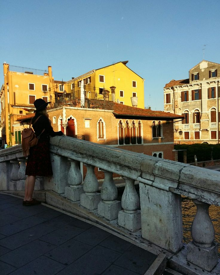 The big canal in Venice, with a random person standing there looking away , full of spirit