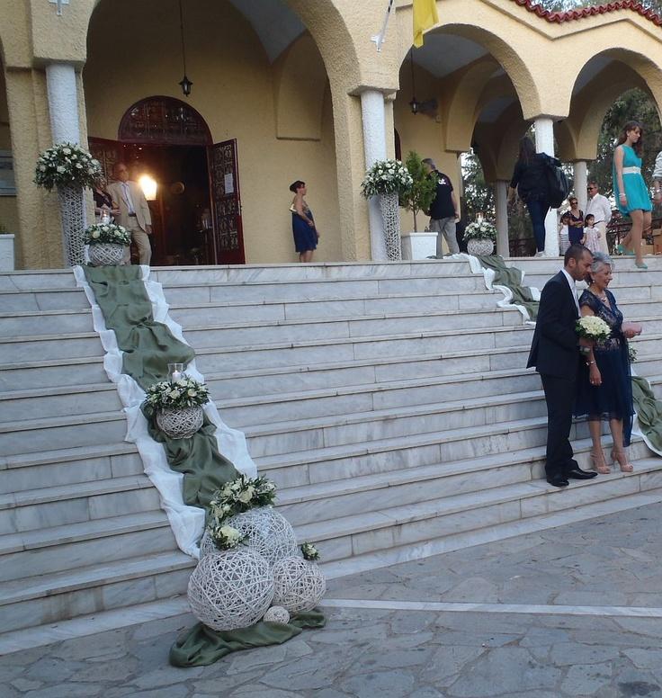 Εξωτερικός στολισμός στα σκαλιά της εκκλησίας με λαδί και λευκά υφάσματα, και πάνω τους λευκές μπάλες μπαμπού με συνθέσεις από φρέσκια λουλούδια σε λευκό