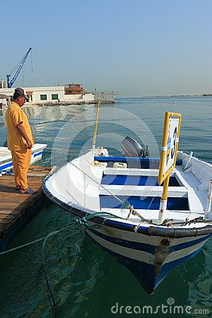 Employee maintenance staff is standing next to the boat, owned by the Flamingo Beach Resort in Old Town Area. Water area of the Persian Gulf. Umm al Quwain. United Arab Emirates
