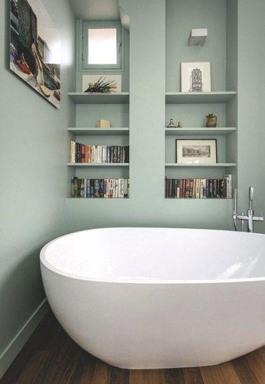 Une baignoire îlot dans une petite salle de bain vert pastel