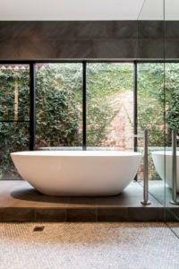 Eine Mitte, großes Bad mit einer erhöhten dunklen Fliesen-Rampe für eine freistehende Badewanne. / Foto: Designmas
