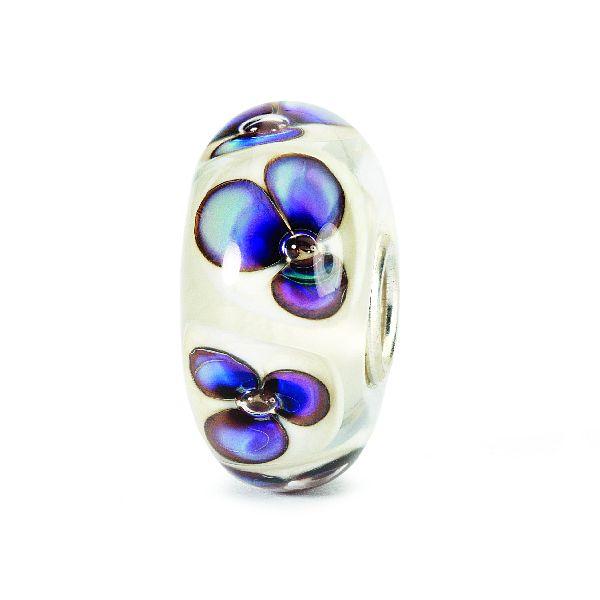 Jemné fialkové fialky se tiše třepetají ve větru a vrhají stín na slonovinový podklad se zábleskem perleti.
