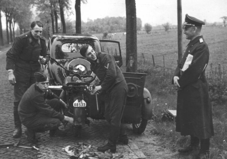Luftwaffe Oberfeldwebel busy repairing the motorcycle German soldiers on the road.