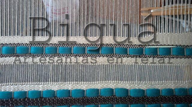 Tapiz realizado en telar maría. Además de la diversidad de lanas y texturas, este tapiz cuenta con vainillas simples como adorno.