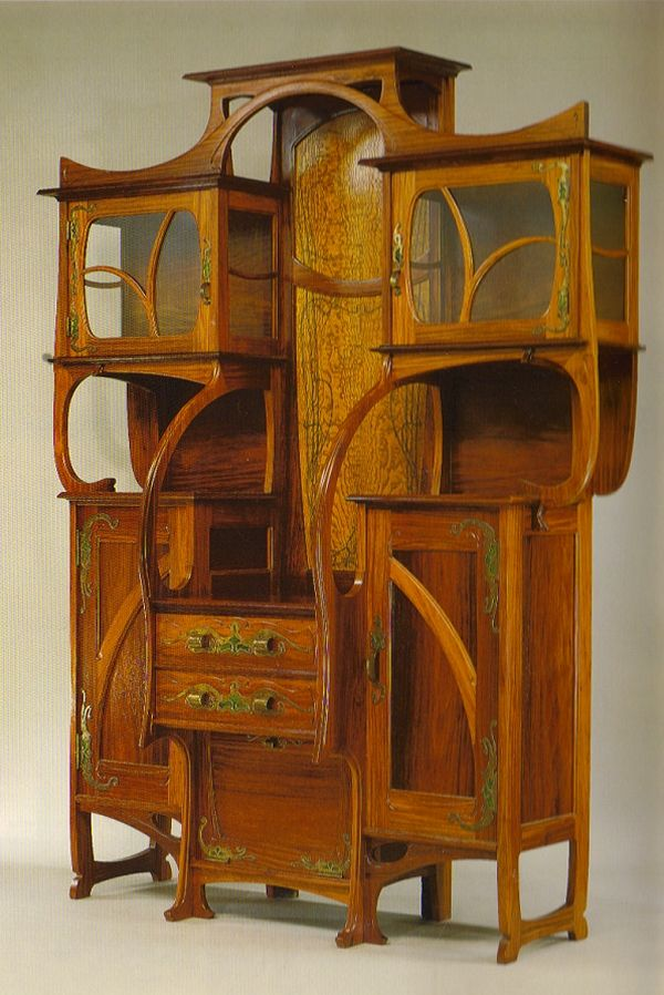 The beautiful piece shown above is displayed in the Metropolitan Museum of Art, NY. It is by Gustave Serrurier-Bovy (Belgian, 1858 - 1910) Note the metal work with enamel and the glass-fronted top display cupboards that also have glass on the sides.