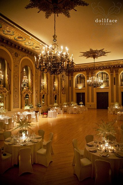 An alluring glow of centerpieces with luxurious white orchids in the Gold Ballroom at Hotel DuPont