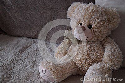 Sweet teddy bear between pillows