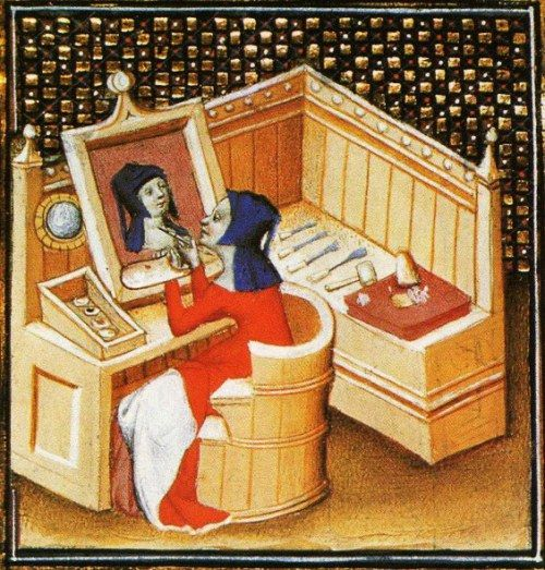 "Marcia paints her self portrait with a mirror. From Boccacio, de mulieribus claris/Le livre de femmes nobles et renomées (trad. anonyme), early 15C French (Paris). Bibliothèque nationale, Paris. MS Français 598, fol. 100v. ""cy apres s'ensuit de marcie qui fut de varron vierge perpetuelle. la LXVIe rubriche."""