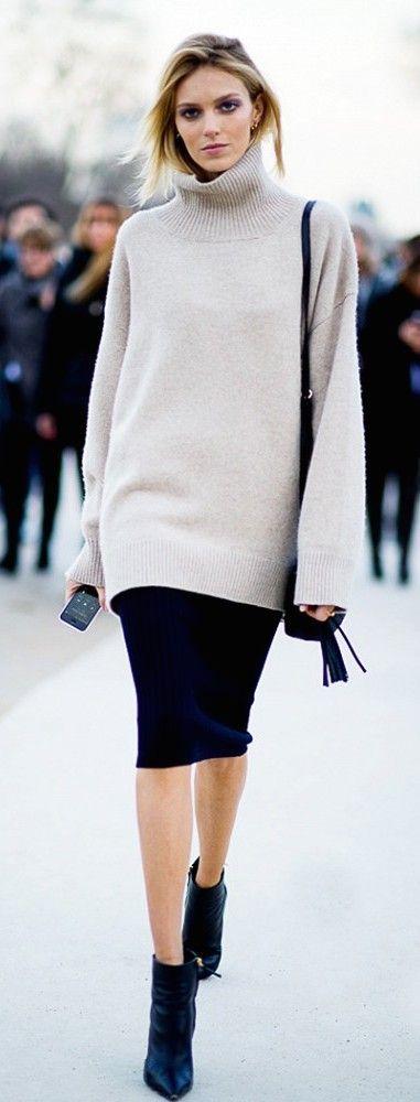 oversized turtleneck sweater worn over a black midi dress
