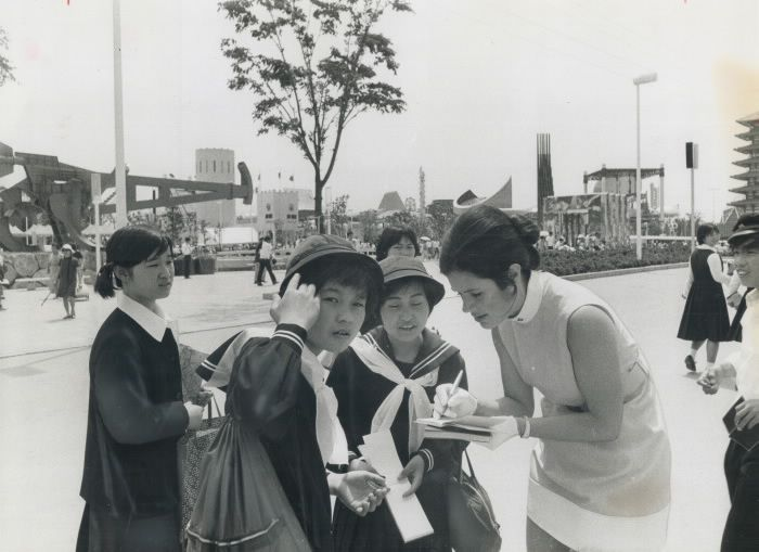 Signing autographs at Expo 70 in Osaka; Japan; is one of the major tasks of Cathy Fauquier; 25; of Toronto; one of the hostesses at the Ontario pavilion there. Like all other school children in Japan; these young girls are in school uniform. Some of the pavilions at Expo can be seen in the background. School children approach any foreigner on the Expo site - particularly Westerners - asking for autographs.