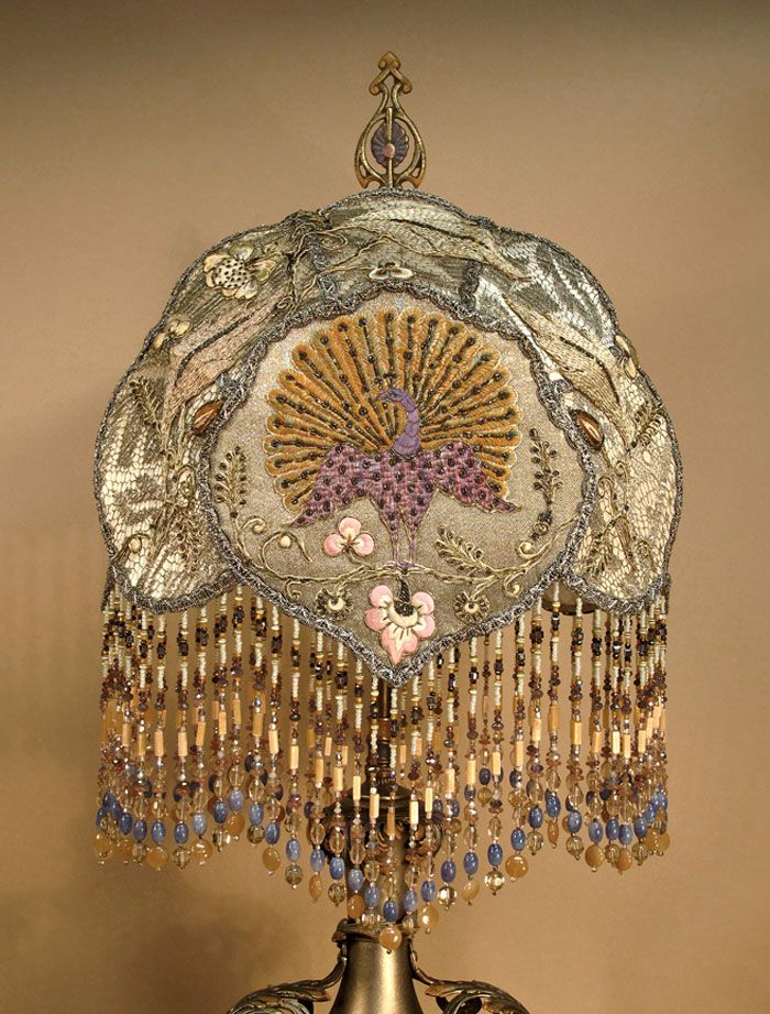 Ivory colored 'CLOUD' shaped shade is covered with silvery metallic lace and overlaid with silk and metallic embroidered appliqués; the center being a tangerine and lavender peacock with foliage. Hand beaded fringe hangs from bottom edge of shade. This sits upon a converted oil-burning lamp, metal with painted metal applications and handles.