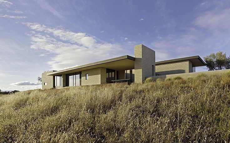 This rural home sits on an 80-acre vineyard site in California's Central Coast wine region. The design directly responds to the wide diurnal temperature fluctuations of its arid climate. Multi-cell masonry block walls, partially filled with insulating spray foam, create the primary building structure and aesthetically anchor the home to surrounding earth, centering activities around …