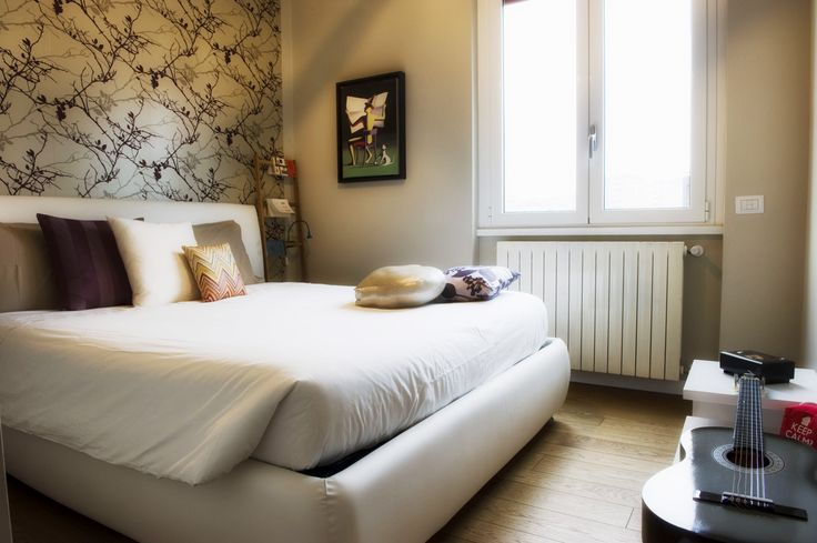 La camera da letto è declinata in toni naturali che si armonizzano con il legno del parquet, trattato con olii naturali per ricreare un nido rilassante e riservato. Il letto tessile, dalle linee morbide e accoglienti, con alta testiera imbottita, poggia su una parete rivestita con carta da parati a disegni floreali, che dona all'insieme un tono romantico. La finestra ha un serramento ad alta efficienza energetica.