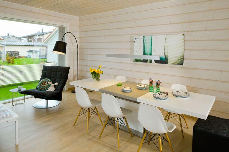 Suuret ikkunat tuovat ruokailutilaan ja olohuoneeseen paljon päivänvaloa. Harri Koskisen suunnittelemassa mustassa K-tuolissa on mukava lueskella. Ruokapöytää ympäröivät Eamesin DSW-tuolit. Pientalo ja piha 5/2015