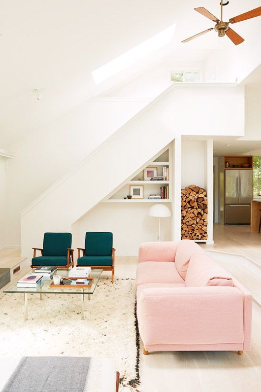 Blush sofa and emerald green armchairs add color to neutrally toned living room.
