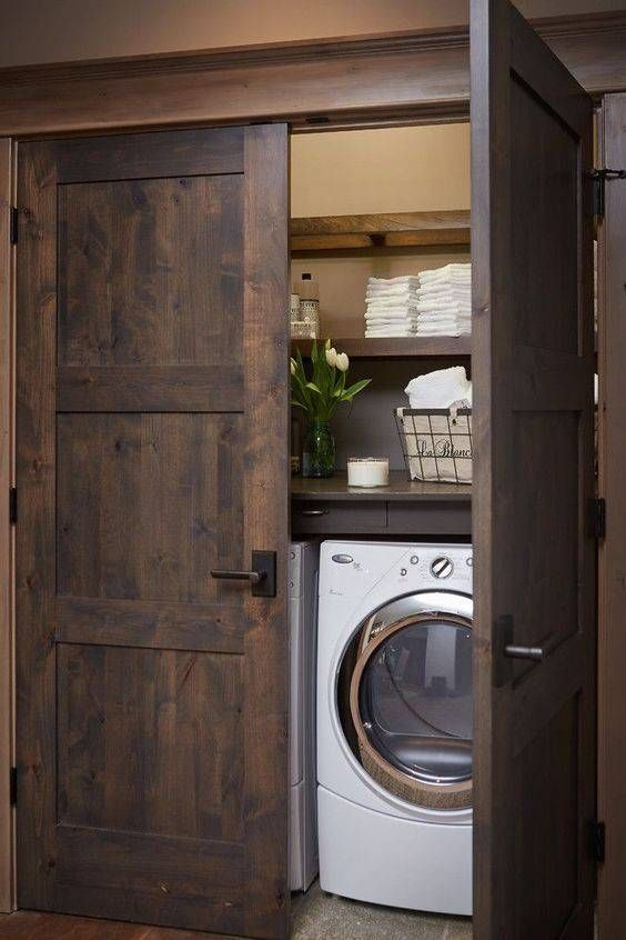 barnwood doors hide a laundry nook and echo with the shelves inside