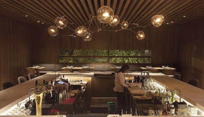 Nos recibe la caja del bar tenuemente iluminado por una lámpara de Lindsey Adelman, donde la madera en techo y paredes es protagónica. Para seguir a los dos salones y a la terraza es necesario cruzar el pasillo metálico integrado a un costado de la cocina, donde se atestigua la preparación de los alimentos.