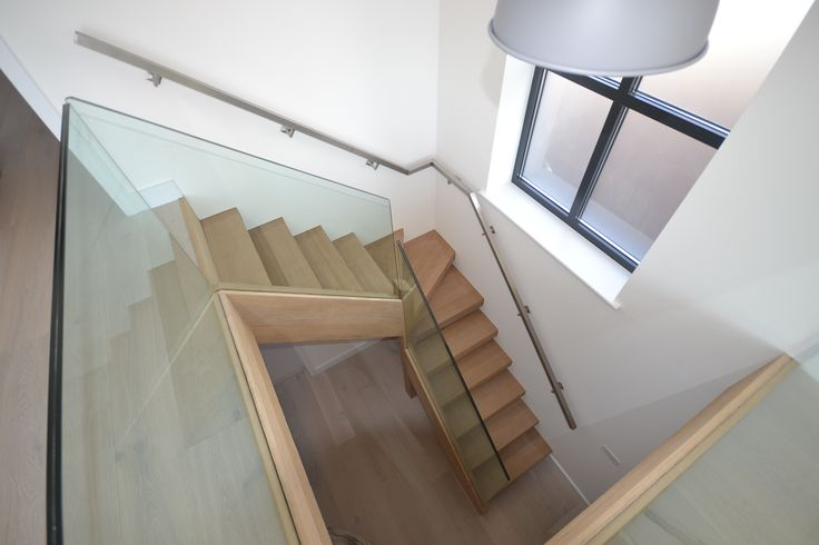Contemporary L shape staircase with glass banister. Matching flawlessly with the style of this modern West Wittering home.