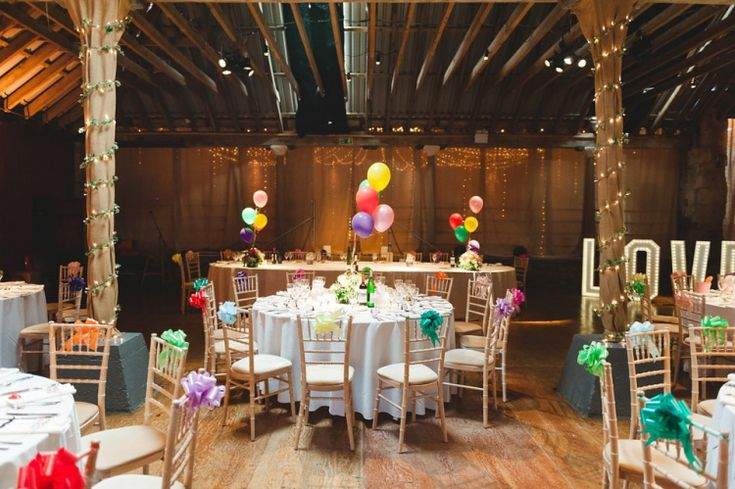 Rustic Scottish barn transformed in to a colourful wedding venue using balloons, bows and giant light up letters.  Photography by http://mackphotography.co.uk/info/