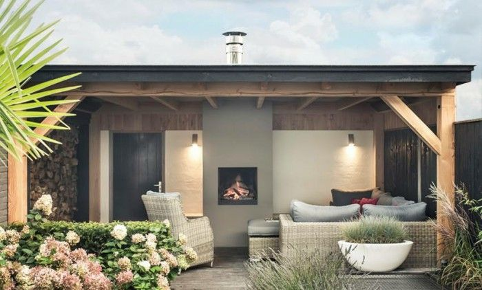 Sfeervolle veranda met hout kachel in strakke tuin. Gemaakt door buitenpracht-houtbouw