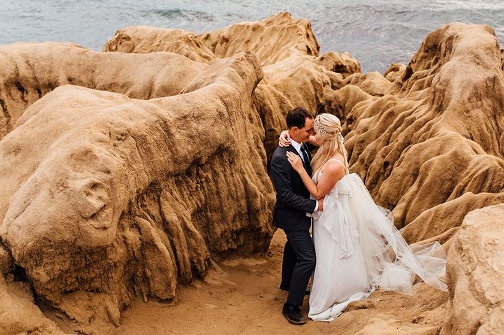 San diego bohemian wedding shoot at sunset cliffs bride chiffon gown with ruffles and thin straps with low back design and plunging neckline and flower headpiece decor with groom charcoal grey suit with matching vest and white dress shirt with long teal tie hugging